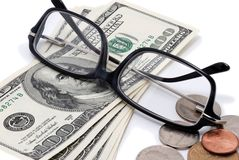 Glasses, hundreds and coins over white. Stock Photo