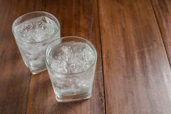 Glasses with ice cubes on wooden background Stock Photo
