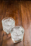 Glasses with ice cubes on wooden background Stock Photography