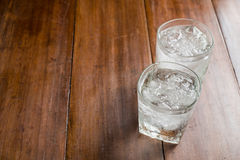 Glasses with ice cubes on wooden background Royalty Free Stock Image