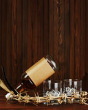 Glasses with ice for whiskey and bottle on wooden background. Stock Images