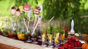 Glasses with ingredients for lemonade, stand on the table. Citrus fruits and mint, strawberries, inside them. Beautiful summer windy weather stock video footage