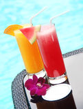 Glasses of juice  by the swimming pool Stock Photography