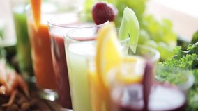 Glasses of juice, vegetables and fruits on table stock footage
