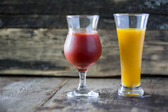 Glasses with juice. Glasses with yellow and red juice on a wooden background royalty free stock photo