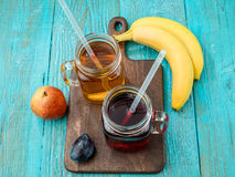 Glasses of juise with fruits on table royalty free stock photography