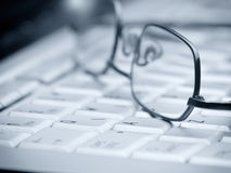 Glasses on the keyboard Stock Photo
