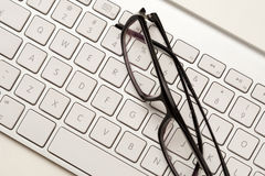 Glasses and keyboard Royalty Free Stock Images