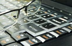 Glasses on keyboard. Black glasses on black keyboard notebook Stock Photography