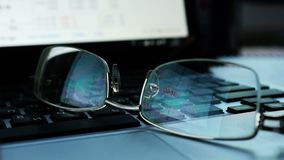Glasses on a keyboard of laptop with Share prices and quotes on a screen. stock footage