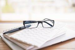 Glasses, keypad, notepads. Closeup of glasses, keypad, pen, notepads and laptop Stock Photos