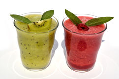 Glasses of kiwi and raspberry juice. With fruits and fresh leaves on top Royalty Free Stock Photos