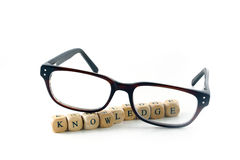 Glasses and knowledge message written in wooden blocks, isolated Royalty Free Stock Photos