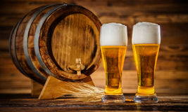 Glasses of lager with old wooden keg Stock Images
