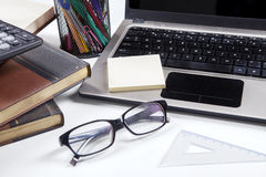 Glasses with laptop and books on table Royalty Free Stock Photo
