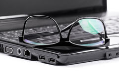 Glasses on a laptop. Close-up shot of glasses on a laptop Royalty Free Stock Photo