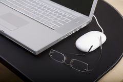 Glasses and Laptop Computer. Glasses and a mouse sitting next to a laptop computer Royalty Free Stock Photos