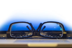 Glasses on laptop keyboard Stock Images