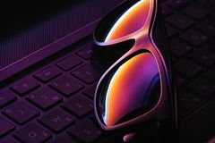 A glasses on the laptop keyboard with ultraviolet light on it. A glasses on the laptop with english and russian symbols and letters keyboard with ultraviolet royalty free stock image