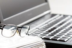 Glasses and laptop on workspace abstract business accounting background Stock Photography