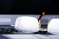 Glasses lay on the keyboard. Business glasses lay on the keyboard of laptop Stock Photo