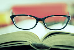 Glasses are laying on a book Cross Prozessed Stock Photos