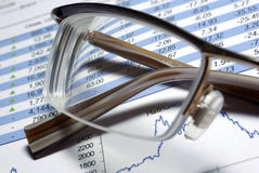 Glasses laying on financial report. Some graphs and data Stock Images