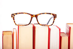 Glasses are laying on a isolated  book staple Royalty Free Stock Photos