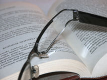 Glasses laying ona book 2. Black trendy glasses laying on a book Stock Photos