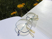 Glasses laying on open book with garden flowers in the background. Glasses laying on open book on the garden ground with yellow dandelions in the back Stock Photos