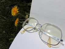 Glasses laying on open book with garden flowers in the background. Glasses laying on open book on the garden ground with yellow dandelions in the back Royalty Free Stock Photos