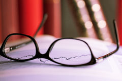 Glasses laying on a share index Royalty Free Stock Image