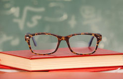 Glasses laying on a staple of Books Royalty Free Stock Image