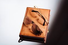 Glasses and leather notebook on a light background royalty free stock image