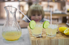 The glasses of lemonade. Boy looks at the glasses of lemonade in the background Stock Photography