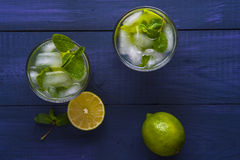 Glasses of lemonade with lemon and lime. Two glasses of homemade lemonade with slices of lemon and lime, mint leaves and ice cubes on wooden background. Top view stock photo