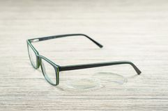 Glasses and lenses for eyeglasses, closeup on the wooden table stock photos