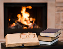 Glasses lie on a book by the fireplace Stock Photos