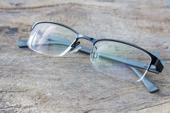 Glasses lie on the dark wooden table. Black glasses on wooden table. Office workplace with glasses on wood table royalty free stock photos