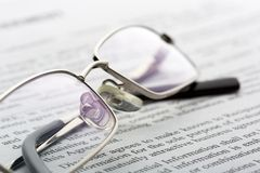 Glasses lies on the newspaper Royalty Free Stock Image