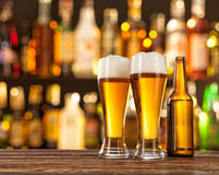 Glasses of light beer with bar on background. Glasses of light beer served on wooden desk. Bar on background Stock Photos