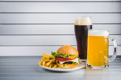 Glasses of light and dark beer with cheeseburger and French fries on aluminum panels Royalty Free Stock Photo