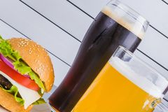 Glasses of light and dark beer with cheeseburger and French fries on aluminum panels Stock Image