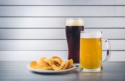 Glasses of light and dark beer with chips on aluminum panels Stock Image