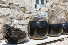Glasses with liquor. Several glass bottles with liquor, carob, walnut liqueur and cherry brandy, matured in sun according to local tradition in Croatia midland Stock Photo