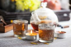 Glasses with lit candles and tea pot. On wooden background stock image