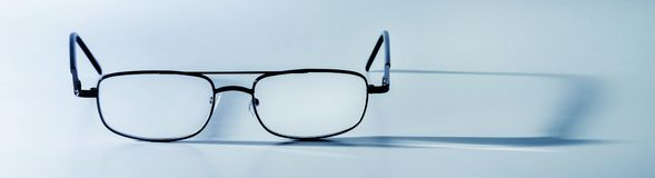 Glasses with a long shadow in a turquoise tone royalty free stock images