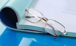 Glasses lying on a book Stock Image