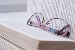 Glasses lying on a book. Glasses lying on an opened book Stock Photos