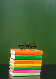 Glasses lying on the books near empty green chalkboard Stock Photos